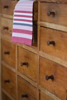 Tea towel hanging out of slightly open drawer of rustic chest of drawers