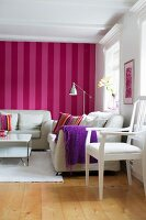 Seating area in Scandinavian living room with white furniture against red and pink striped wallpaper