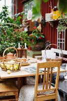 Basket of apples on wooden table and old kitchen chairs in front of wooden cabin