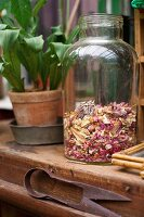 Dried petals in old glass jar on wooden surface