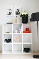 Black bowls on white, modern shelving next to standard lamp with black lampshade