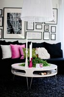 Round, modern coffee table on dark, long-pile rug in front of black sofa with row of scatter cushions below gallery of pictures on wall