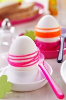 Boiled eggs wrapped in brightly coloured woollen yarn in pink and white eggcups with plastic spoons