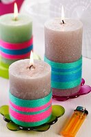 Candle wrapped in colourful woollen yarn on colourful, transparent candle holders