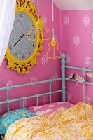 Child's bed with retro, turquoise metal frame in corner below large wall clock with yellow frame on pink wallpaper with ornamental pattern