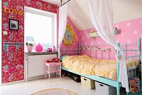Turquoise, metal-framed bed against pink wallpaper in nostalgic girl's bedroom