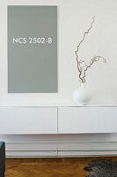 Twig in vase on white, minimalist floating sideboard below grey panel with NCS colour code on wall
