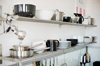 Black and white crockery on metal wall rack in corner of kitchen