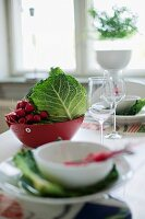 Place setting with white bowl in front of red bowl of vegetables on table