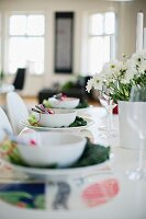 Place settings decorated with white bowls and savoy cabbage leaves and vase of flowers on table