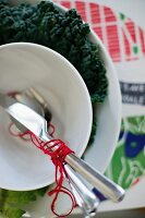 Cutlery wrapped in red yarn in white soup bowl