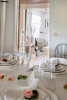 Place settings and roses on white dining table; view into rustic living room through open door in background