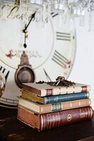 Stack of antiquarian books and bunch of keys on surface in front of old clock face