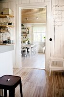 Rustic kitchen with retro stool on wooden floor and view into dining room through open door in background