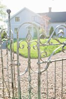 Country house seen through wrought iron gate