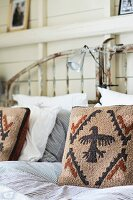 Scatter cushions with heraldic bird motif on striped bed linen