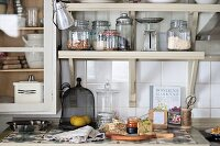 Food preparation on kitchen worksurface below storage jars on bracket shelves
