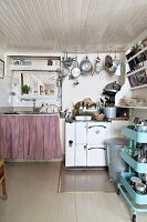 Retro, pale blue tea trolley, cooker and pots and pans hanging from rod in rustic kitchen