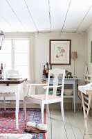 White-painted chairs next to table in front of window in rustic dining room with white board floor and ceiling
