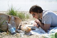 Man on a beach picnic reading a book