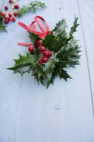 Holly sprigs with berries and leather ribbon (Christmas decoration)