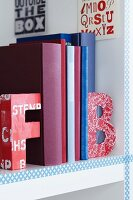 Colourful alphabet bookends on white bookshelf