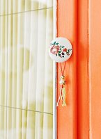 Retro furniture knob with floral motif and small tassel on cupboard door