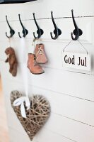 Vintage child's shoes and sign with motto hanging from coat pegs on white wooden wall