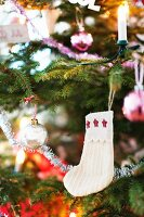 White baby's socks with stars hanging on decorated Christmas tree