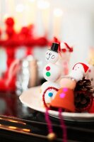 Snowman figurine made from white balls and other Christmas decorations on plate