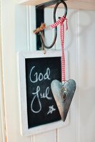 Heart-shaped pendant with red gingham ribbon hanging from wall bracket in front of Christmas greeting on blackboard