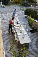 View down onto long, weathered wooden table and white chairs on wooden deck in Mediterranean garden; women setting table