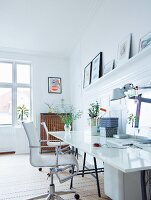 White desk and swivel chair in room with wooden floor