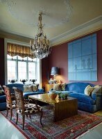 Antique armchairs with modern upholstery and blue sofa set around coffee table in grand interior with modern ambiance