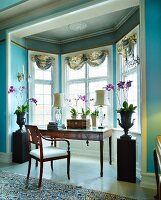 Purple potted orchids flanking workspace with antique writing desk and chair in window bay of grand salon with walls painted light blue
