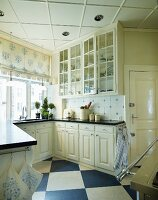 Antique, white, country-house kitchen with diagonal chequered floor