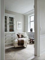 View through open door of white armchair with matching footstool next to dresser with glass-fronted top in traditional interior