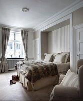 Bedspread and stacked pillows on box-spring bed in niche in traditional bedroom with subdued colour scheme