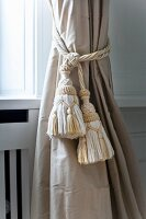Cord tieback with elegant tassels on curtain on window