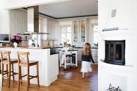 Girl in open-plan, white country-house kitchen with wooden bar stools at breakfast bar integrated into kitchen counter