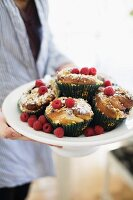 Person holding dish of muffins and fresh raspberries