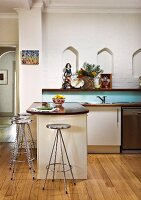 Retro chrome bar stools at kitchen counter on wooden floor, wooden shelf below small ogee niches in wall in background