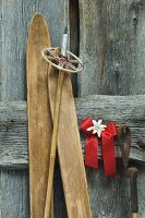 Antique skis and ski poles leaning on wall next to Christmas decoration