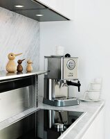 White kitchen with marble back wall and worksurface, stainless steel shelf, integrated hob and espresso machine