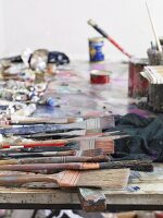 Painter's utensils on long wooden table in artist's studio