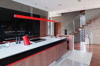 Long kitchen counter with wooden base cabinets below pendant lamp with red-painted narrow housing in modern kitchen with staircase in background