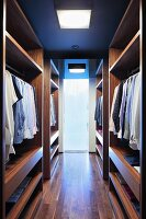 Elegant dressing room with wooden, open-fronted wardrobes