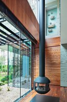 Suspended, cast iron fireplace in contemporary house next to glass facade with view of garden