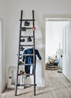 Pairs of child's shoes and Babygro hanging from old attic ladder; old rocking chair seen through open door