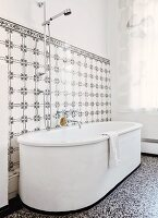 White, free-standing bathtub on terrazzo floor against wall tiled in black and white vintage pattern